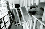 A man holds a mirror between jail cell bars