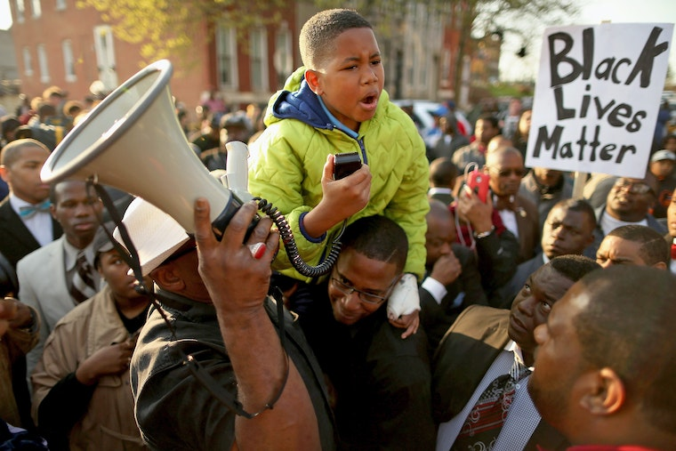 A young boy sitting atop another man's shoulder in a crowd speaks into a megaphone.