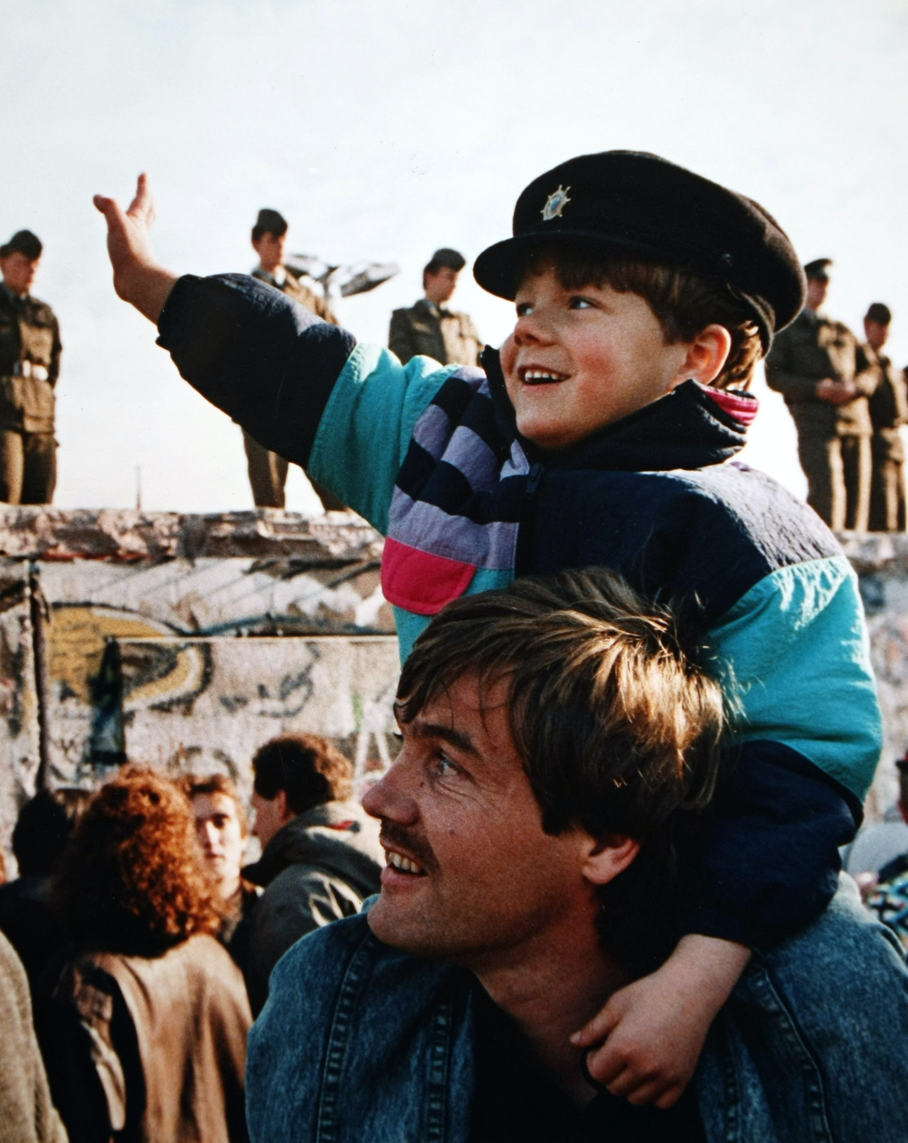 A boy waving to soldiers standing on the Berlin Wall