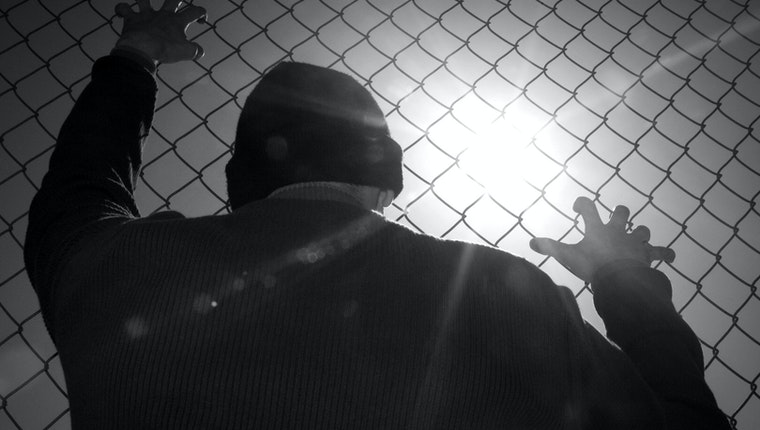 Man against a chain-link fence