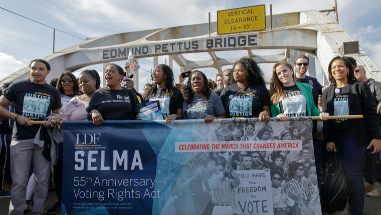 People holding a sign commemorating the 55th anniversary of the Voting Rights Act