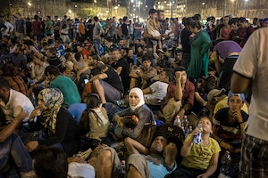 crowd of migrants at night outside a Budapest train station