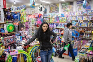 A young woman surrounded by brightly colored toys