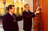 George Soros unlocking a large carved door