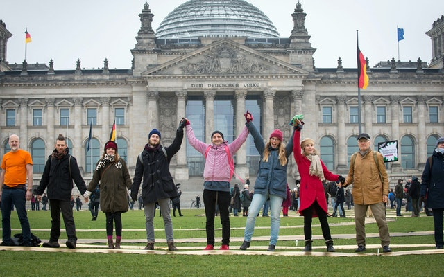 A group of adults holding hands in front of the Reichstag building