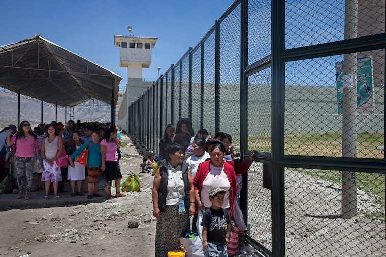 Women and children standing in lines outside a prison fence.