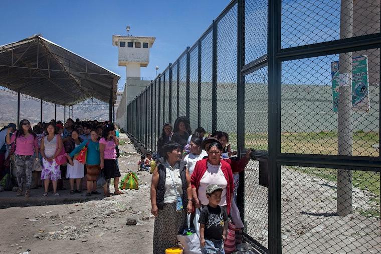 Mujeres y niños parados en fila tras una cerca de la prisión.