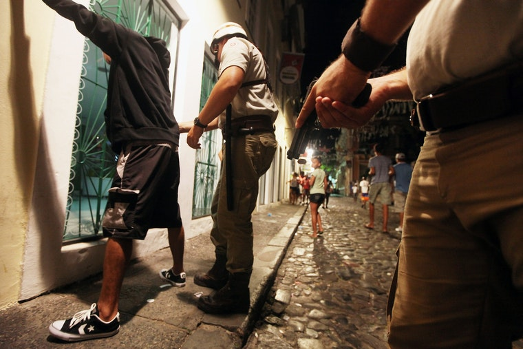 A man is searched by police at night