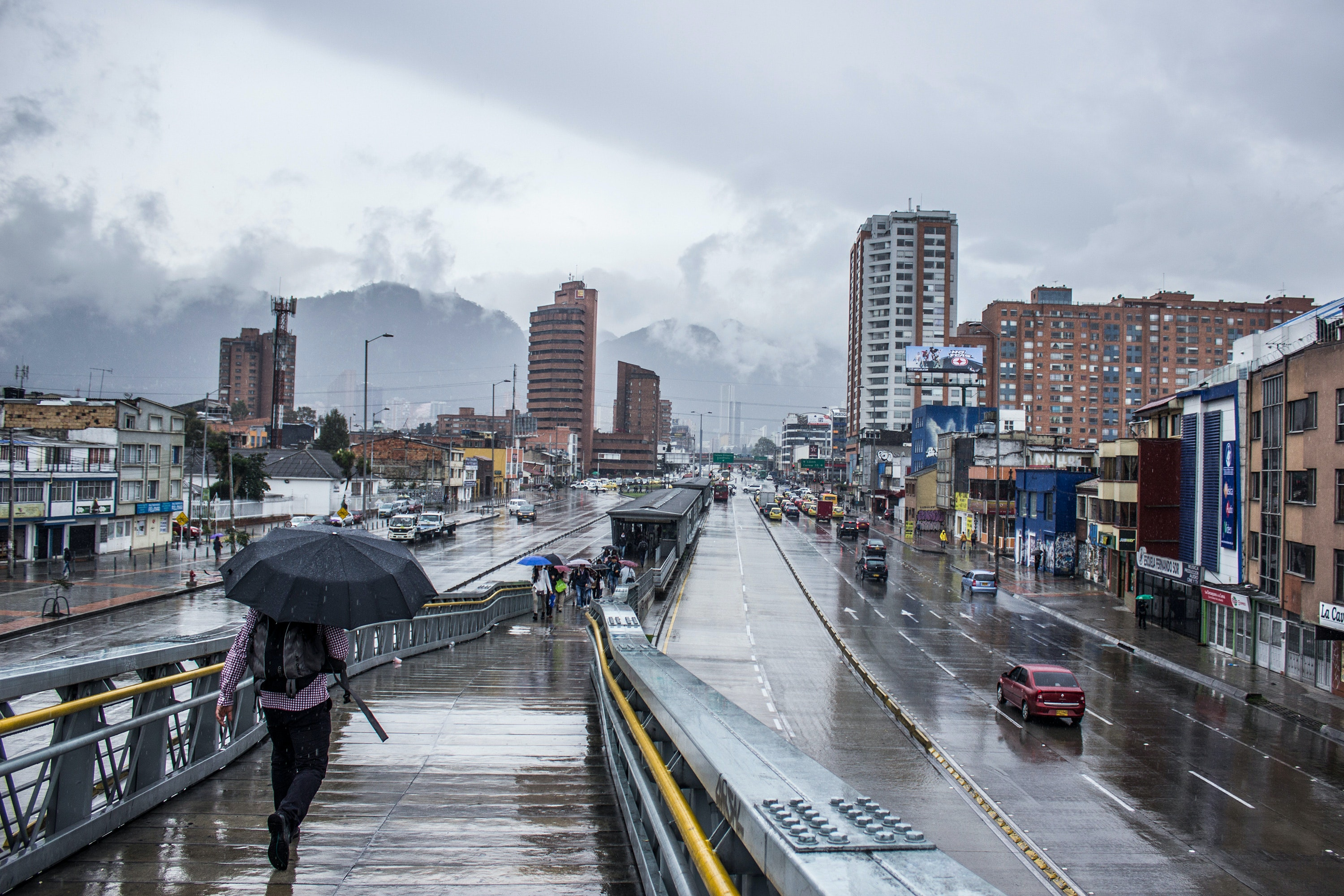 A person walking with an umbrella in Bogota, Colombia.
