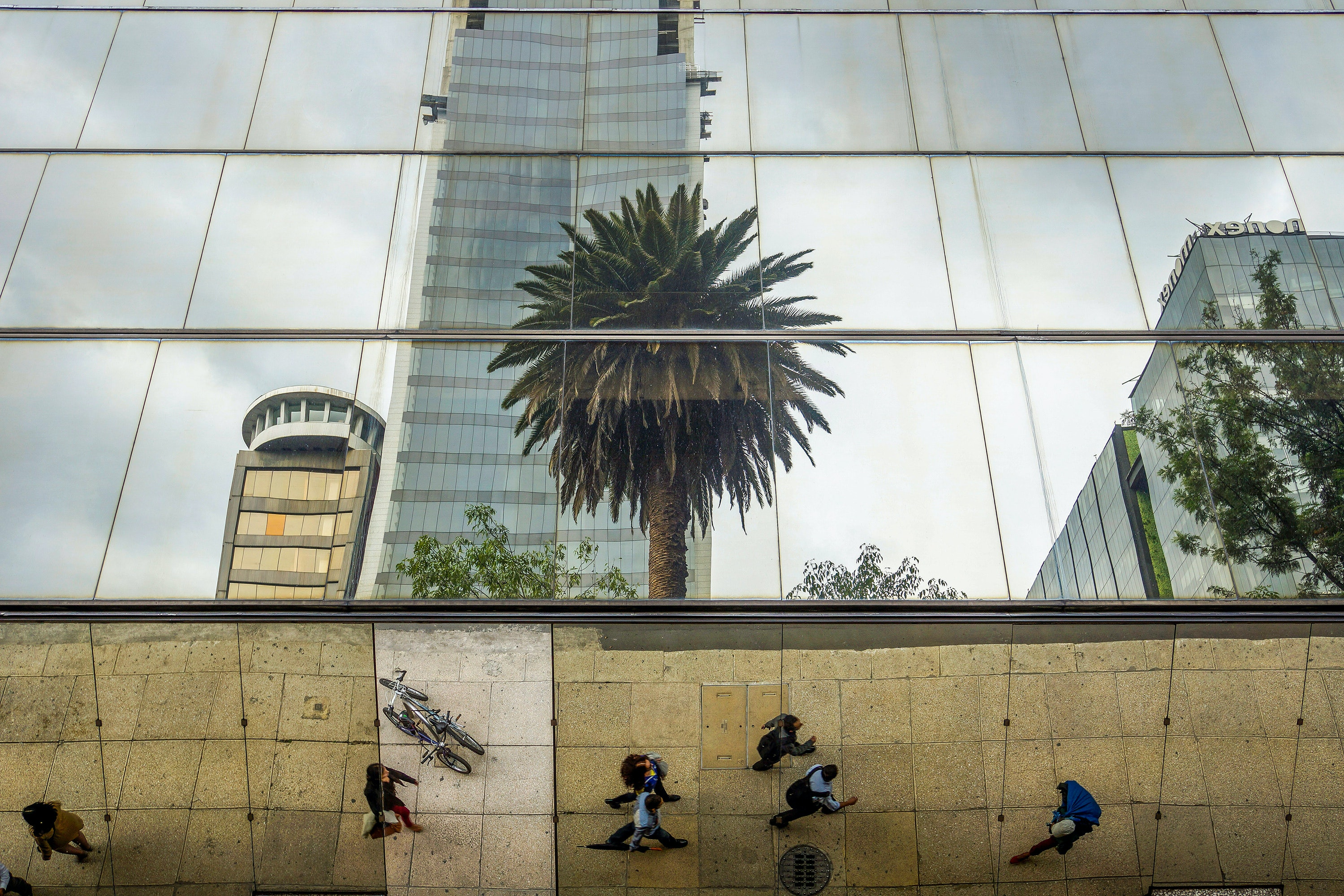 People on the sidewalk next to mirrored buildings in downtown Mexico City.