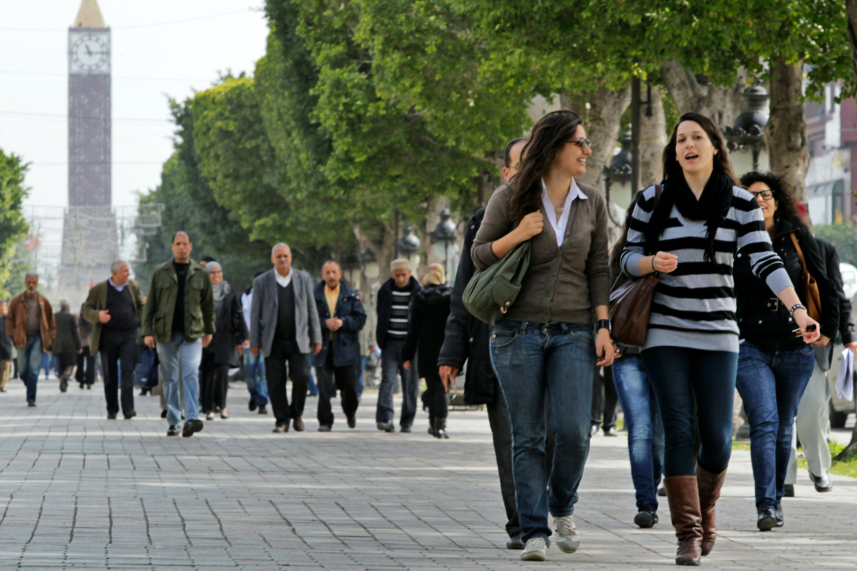 People walking on a shaded pedestrian area.