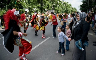 Families interacting with carnival performers