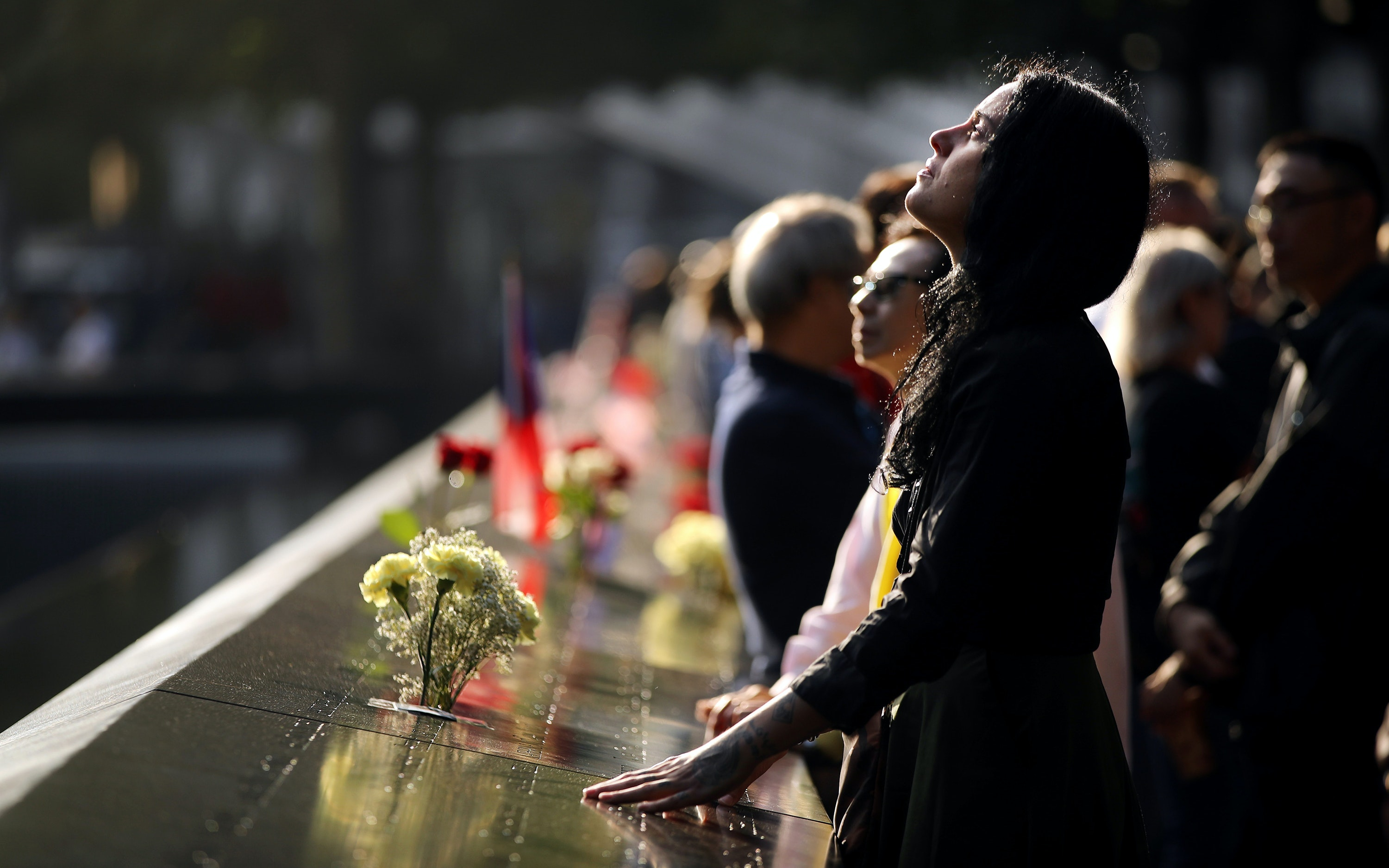 A woman standing at the September 11 memorial