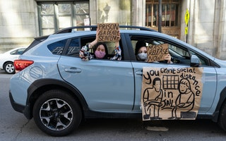 People hold signs from a car window