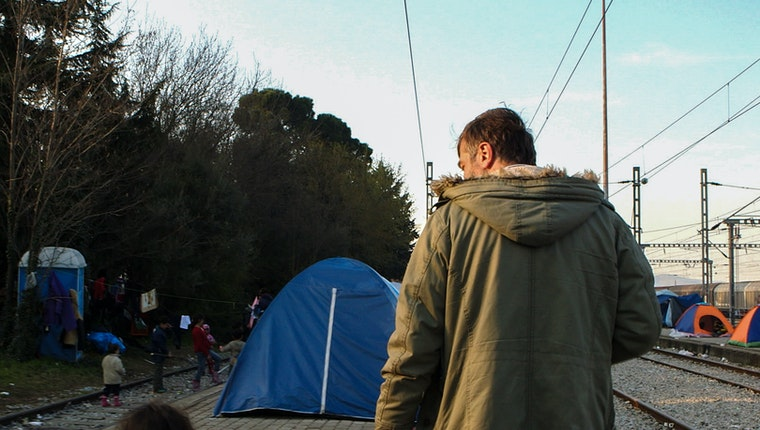 Man walking through refugee camp by railroad tracks