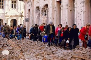 A line of Croatians walk through rubble