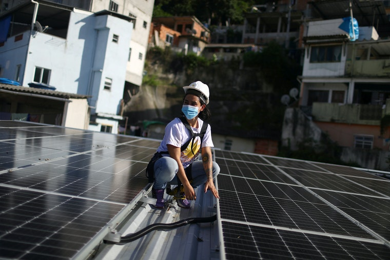 A woman wearing a hardhat on a roof covered in solar panels