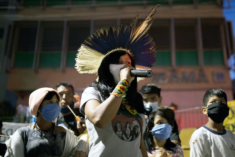 A climate activist holds a microphone among a crowd