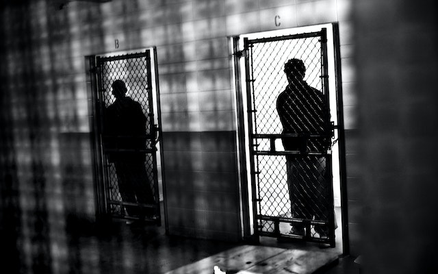 Silhouetted figures in adjacent prison cells