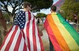 Two men walking wearing flags
