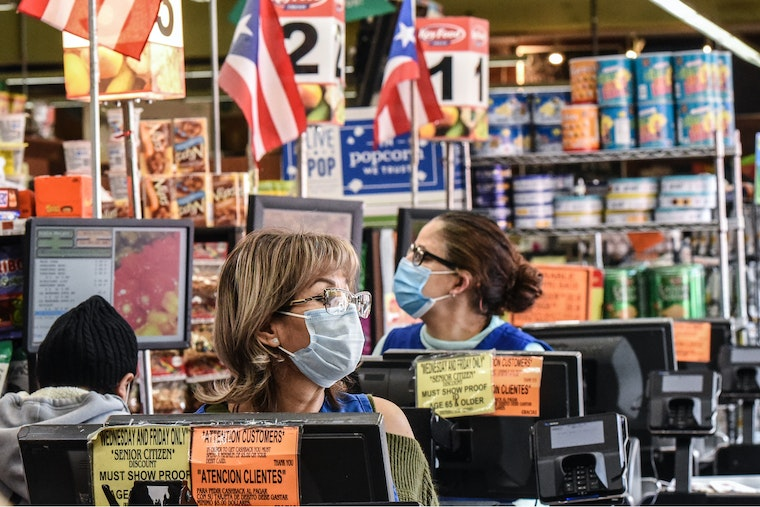 Two women at the registers in a grocery store