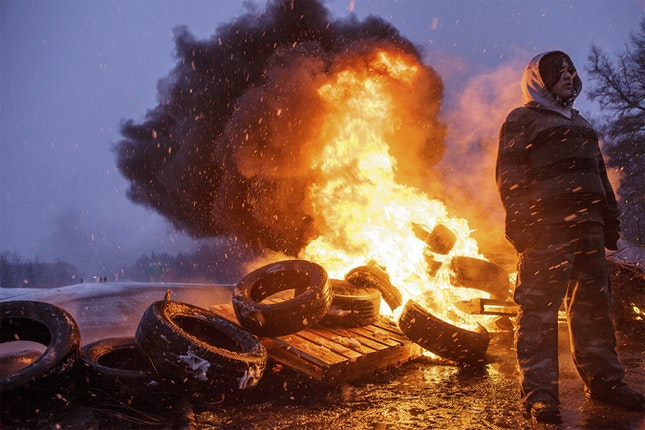 Person stands near burning tires
