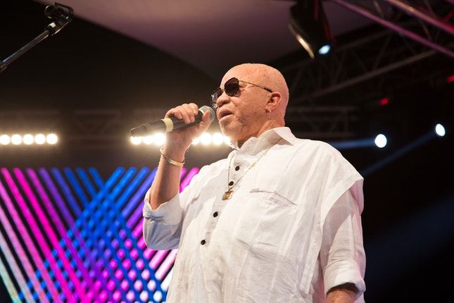 Salif Keita holding a microphone on stage