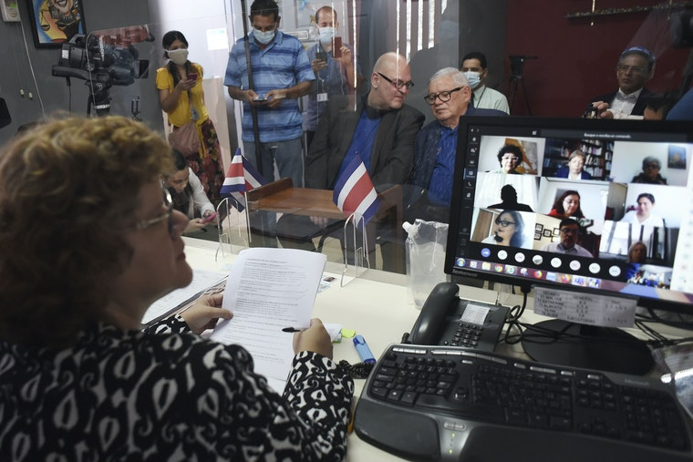 A woman sits at a desk in front of two men on a bench among a small group of onlookers and a video camera