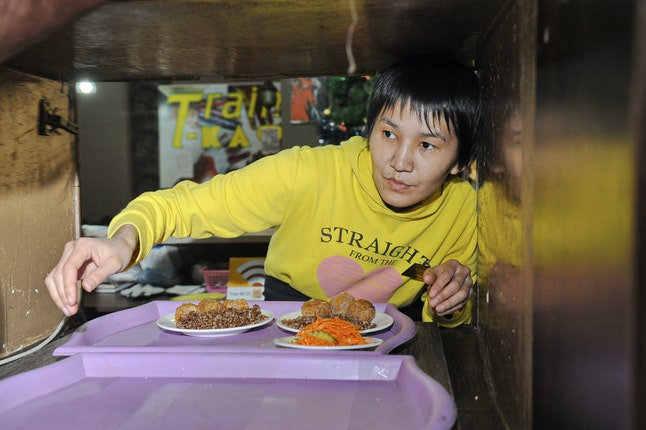 A women passes a tray of food through a window
