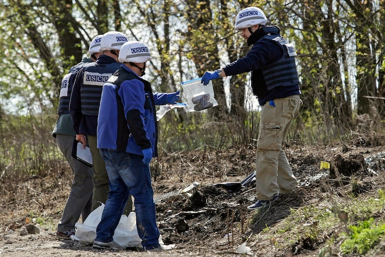Three people in safety vests and helmets collect evidence