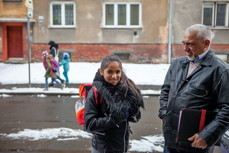 A father and daughter stand next to one another on a snow covered street.