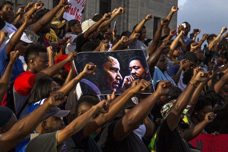 A group of people hold a sign featuring the Rev. Dr. Martin Luther King, Jr., and former U.S. President Barack Obama and raise their fists in the air.