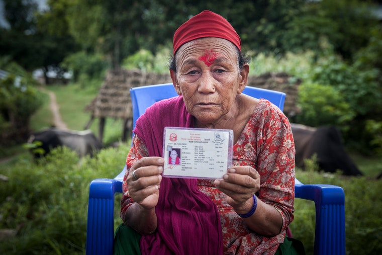 A woman holding an id card in her hands while facing the camera.