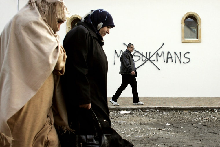 A group of Muslim people walk down a street, past a wall with a racial slur painted on it.