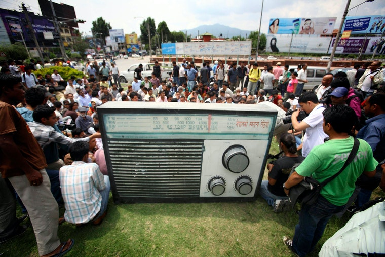 A crowd of people gather outdoors, around a large replica of a radio.