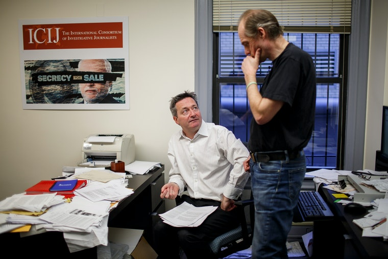 Two men in an office talk; one is standing, the other is sitting.