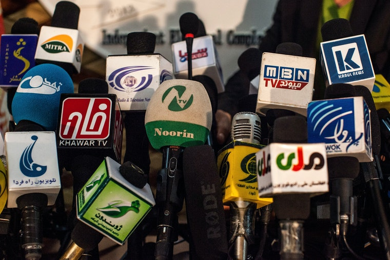 Multiple television and radio microphones, belonging to multiple Afghan media entities, are assembled together.
