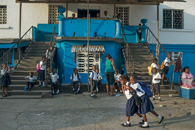 Students linger on the steps in front of a school building.