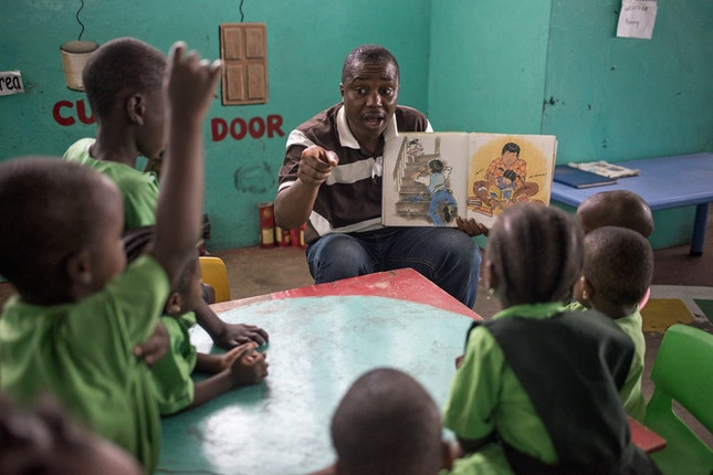 A teacher reading a book to a group of school children