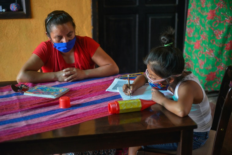 A mother watches her daughter do schoolwork at a table