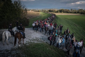 Line of refugees walking on a road
